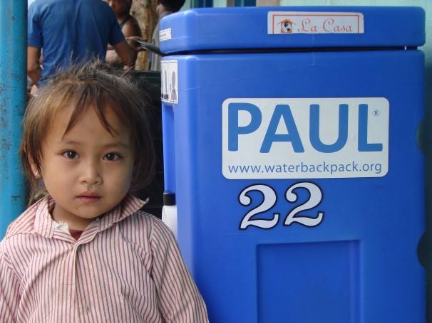 Ein Kind steht neben dem Wasserfiltersytsem PAUL