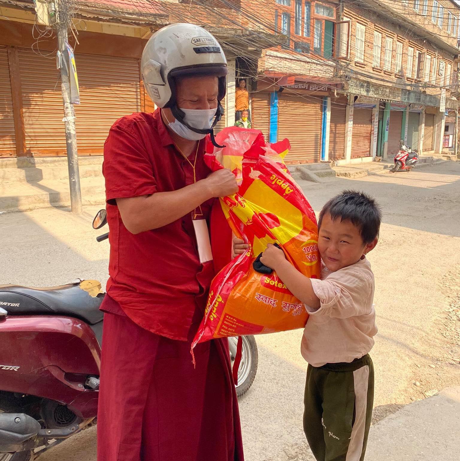 Der buddhistische Mönch Geshe Sonam Wangchen gibt Lebensmittel aus